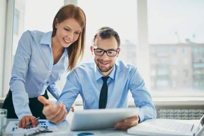 ブルーのワイシャツを着てデスクで資料を一緒に見る男女画像