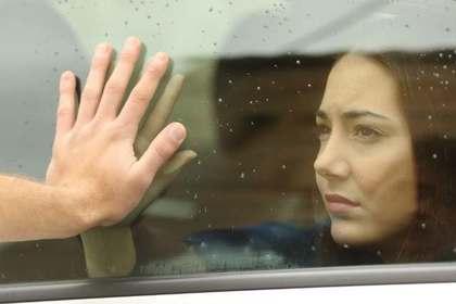 車窓越しに別れを惜しむ二人