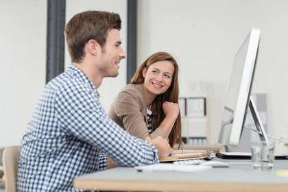 パソコンを見る男性を見て微笑む女性画像