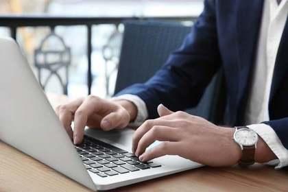 腕時計を付けてノートパソコンを打つスーツ姿の男性画像