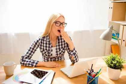 あくびをする眼鏡の女性