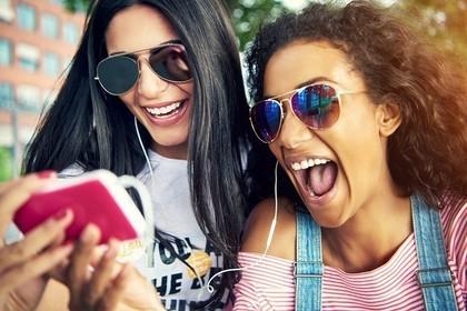 イヤホンで音楽を聴く2人の女性