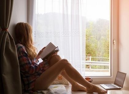 窓辺で本を読む淋しそうな女性