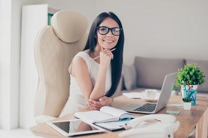 パソコンの置かれたデスク前に座り眼鏡をかけて微笑む女性画像