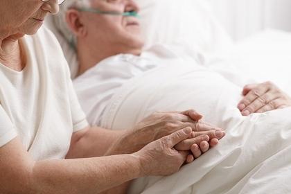 病院のベッドにいる男性の手を取る女性