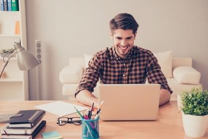 パソコンを見て嬉しそうな男性