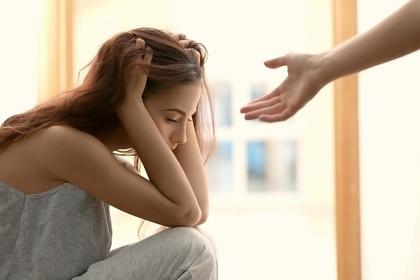 落ち込んでいる女性に手を差し伸べている人