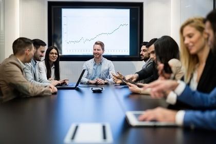 モニターがある会議室で会話をする大勢の男女