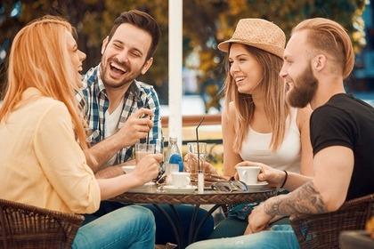 外のカフェで談笑する4人