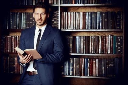 本棚の前で本を持ち立つスーツ姿の男性画像