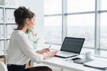 窓際の席でパソコンを打つ女性画像