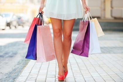 大量のショッピングバッグを持って歩く女性