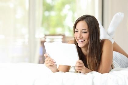 タブレットをしながら笑顔の女性