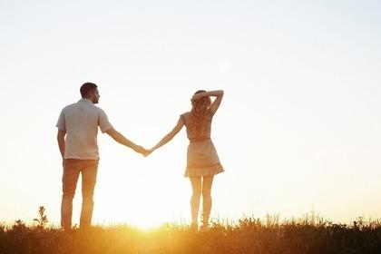 夕日と手を繋ぐ2人