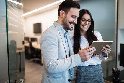 オフィスで一緒にiPadを見て微笑む男女画像