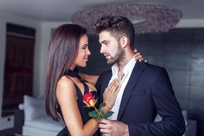 バラの花を持った男性と抱きつく女性