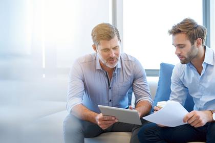 ソファに座り書類を見て話し合う2人の男性画像