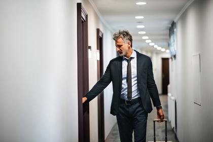 キャリーケースを引いて廊下を歩くスーツ姿の男性画像