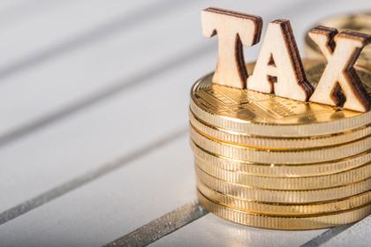 税金を表す単語のオブジェが乗せられたコイン