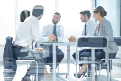 スーツを着て会議をする男女画像