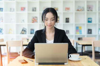 カフェでコーヒーを飲みながらパソコンを打つスーツ姿の女性画像
