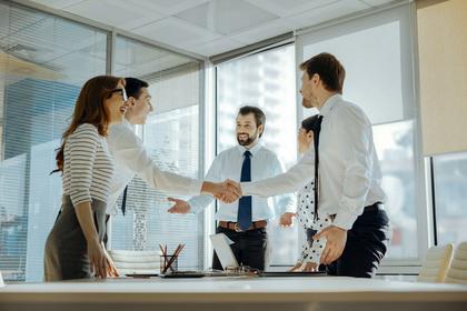 会議で立って握手を交わす男女画像