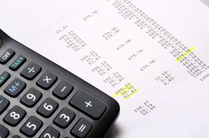 電卓とラインが引かれた数字のリストが写された画像