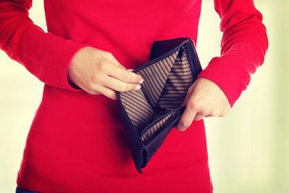 空のお財布を見せる女性