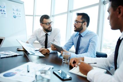 ワイシャツにネクタイ姿で会議をする数名の男性画像