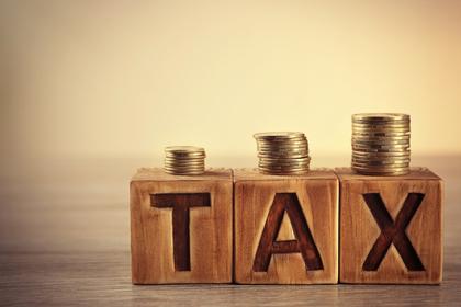 税金を意味する単語を表すオブジェの上にコインが積み上げられている様子