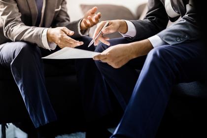 書類とスーツ姿の男性達