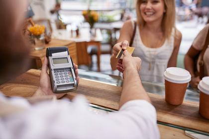 お店で店員にカードを出す女性