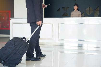 ホテルのフロントに向かうキャリーケースを引いたスーツ姿の男性画像