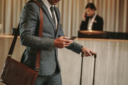 ホテルのフロント前でキャリーケースを引くスーツ姿の男性画像
