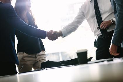 オフィスで立って握手を交わす男性画像