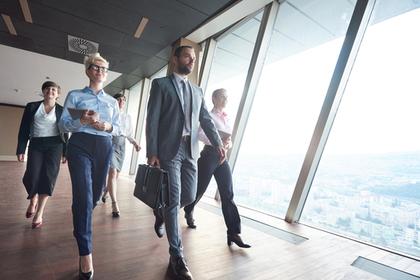 スーツ姿で歩く数人の男女画像