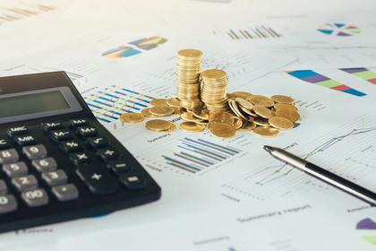 グラフが掲載された書類の上に乗せられた電卓とコイン
