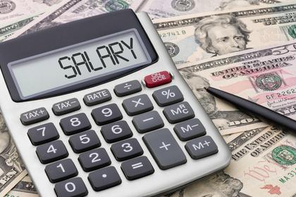 お札の上にお給料を意味する単語が表示された電卓が乗せられている様子