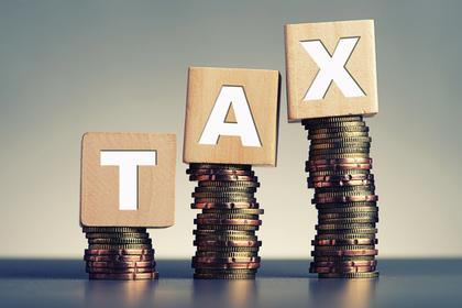 積み上げられたコインの上に税金という意味の単語を表すオブジェが乗せられた様子