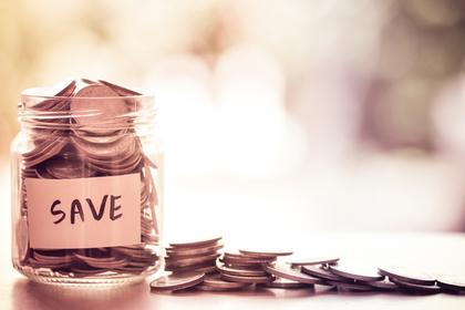 貯金という意味の単語が書かれた瓶にお金が入れられている様子