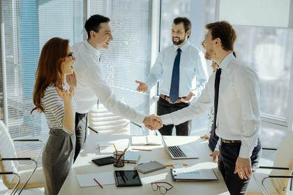 数人の男女が集まる会議室で立って握手を交わす男性画像