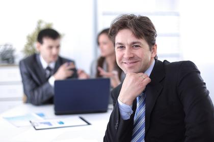 オフィスで振り向き顎に手を当てて微笑むスーツ姿の男性画像