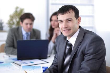 オフィスで振り向いて微笑むスーツ姿の男性画像