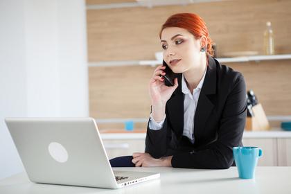 パソコンをしながら電話する女性