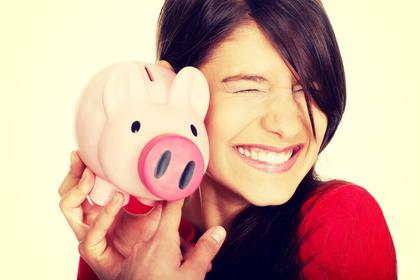 貯金箱を持ち微笑む女性