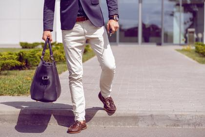 ボストンバッグを持って階段を降りている男性