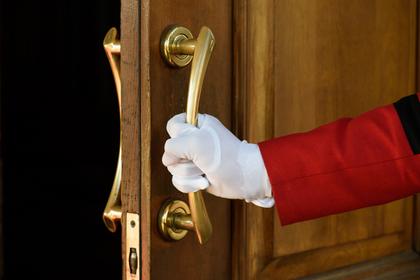 白手袋をしてドアを開ける画像