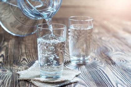 ピッチャーからグラスに水を注いでいる