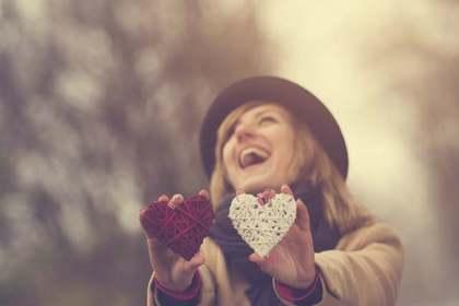 笑顔でハートを持つ女性