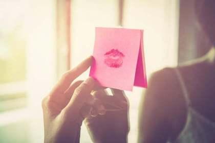 キスマークつきのカードを手にする女性